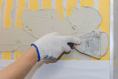 Construction work laying tile on the wall Royalty Free Stock Image