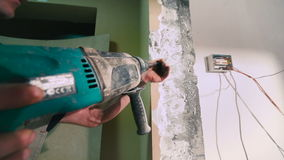 Construction work in the new apartment. Construction worker using a hummer drill. Renovate an apartment stock footage