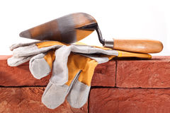 Construction work. Trowel and gloves on the red bricks Royalty Free Stock Photo