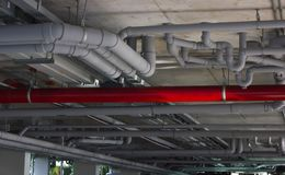 Construction work. Water pipe system. System of gray sanitary pipes in the building.  stock photography