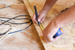 Construction work. Woodwork. Male builder marking point on hardboard. Construction work. Woodwork. Male builder marking point on hardboard Royalty Free Stock Photo