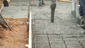 Man is pouring foundation with wet heavy concrete through pipe, closeup view.