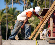 Construction worker. Putting America back to work! A latino construction worker with white helmet building a new resort in a tropical setting with palm trees in Stock Photo