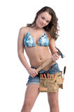 Construction Worker. Cute young woman in Daisy Duke denim shorts, bikini top and a framers tool belt as if she were a construction worker Stock Photos