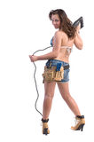 Construction Worker. Cute young woman in Daisy Duke denim shorts, bikini top and a framers tool belt as if she were a construction worker Stock Photo