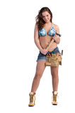 Construction Worker. Cute young woman in Daisy Duke denim shorts, bikini top and a framers tool belt as if she were a construction worker Royalty Free Stock Photography