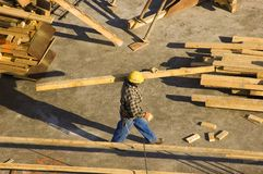 Construction Worker. Walks and carries lumber Stock Photo