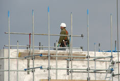 Construction Worker. Worker standing on top of a building under construction royalty free stock photo