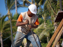Construction worker. Putting America back to work! A latino construction worker with white helmet building a new resort in a tropical setting with palm trees in Royalty Free Stock Photography
