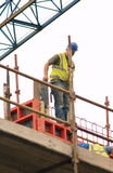 Construction worker. High above ground level and below crane Royalty Free Stock Photos