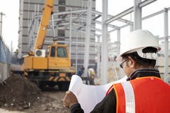 Construction worker. Foreman cheking plant on construction site with worker background and excavator Stock Photography