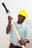 Construction worker. Old african man with a hard-hat holding a pick-axe stock image