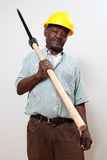 Construction worker. Old african man with a hard-hat holding a pick-axe stock photos