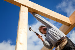 Construction worker. Builder at work with wooden  roof construction Stock Photo