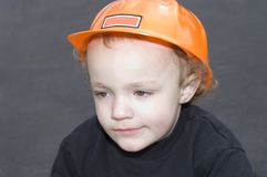 Construction Worker. Young boy wearing orange construction hat against black background Stock Photos