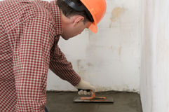 Construction worker. Spreading wet concrete Royalty Free Stock Photo