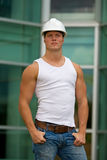 Construction worker. A fit construction worker standing with hands in his pockets stock photo