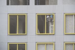 Construction worker abseiling plastering two people royalty free stock photography