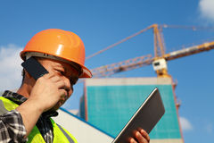 Construction worker. Activity with mobile phone and digital tablet stock image
