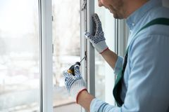Construction worker adjusting installed window with screwdriver indoors. Closeup stock image