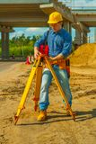 Construction worker adjusting theodolite Stock Photo