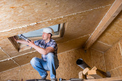 Construction Worker Applying Caulking to Sky Light Stock Images