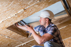 Construction Worker Applying Caulking to Sky Light Stock Image
