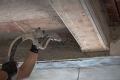 Construction worker applying cement plaster. On the wall surface with plastering machine Royalty Free Stock Photography