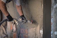 Construction worker applying cement plaster. On the wall surface with plastering machine Stock Images
