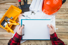 Construction worker architect exploring blueprints plans for a new building. Construction and repair. Workplace professional holding in hands white plate, you Stock Images