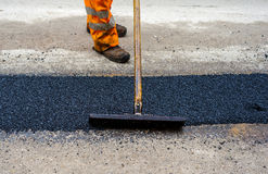Construction Worker during Asphalting Road Stock Images