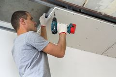 Construction worker assemble a suspended ceiling with drywall an royalty free stock image