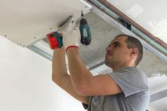 Construction worker assemble a suspended ceiling with drywall an. D fixing the drywall to the ceiling metal frame with screwdriver stock image