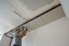 Construction worker assemble a suspended ceiling with drywall an royalty free stock photography