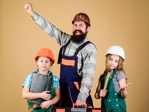 Construction worker assistant. Builder or carpenter. Bearded man with little girls. Repair. Childrens creativity. Construction worker assistant. Builder or royalty free stock photo