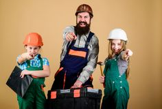 Construction worker assistant. Builder or carpenter. Repairman in uniform. Foreman. Family teamwork. Repair. Father and. Daughter in workshop. Bearded men with royalty free stock image