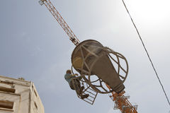 Construction worker being lifted, Lebanon. Construction worker being lifted with a cement container by a crane. Lebanon Stock Images