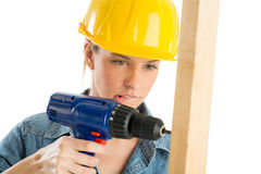 Construction Worker Biting Lip While Drilling Wooden Plank. Close-up of beautiful construction worker biting lip while drilling wooden plank isolated over white Stock Photo