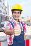 Construction worker with black hair showing thumb up. And the construction site in the background Royalty Free Stock Photos