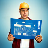 Construction worker with blueprint. Making a funny face Royalty Free Stock Photography
