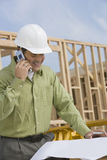 Construction Worker With Blueprints And Cellphone Stock Photo