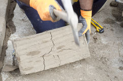 Construction worker breaking a mud brick with pick Stock Photo