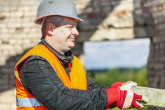 Construction worker with brick in the hands Stock Photo