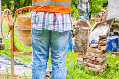 Construction worker with brick near concrete mixer Stock Image