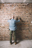 Construction worker on the brick wall background Royalty Free Stock Photo