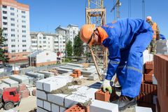 Construction worker bricklayer. Photo bricklayer while working on the edge of the wall Royalty Free Stock Photo