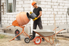 Construction concrete mixer. Construction worker with a bucket in his hands loads a concrete mixer Stock Images