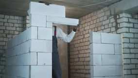 Construction worker building doorway with aerated concrete blocks stock video