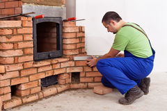 Construction worker building a masonry heater. Construction worker building a traditional masonry heater - checking it with a spirit level Royalty Free Stock Image