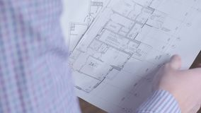 Construction worker and building plans, architect or engineer looking and examining blueprints of new houses and. Apartments stock footage